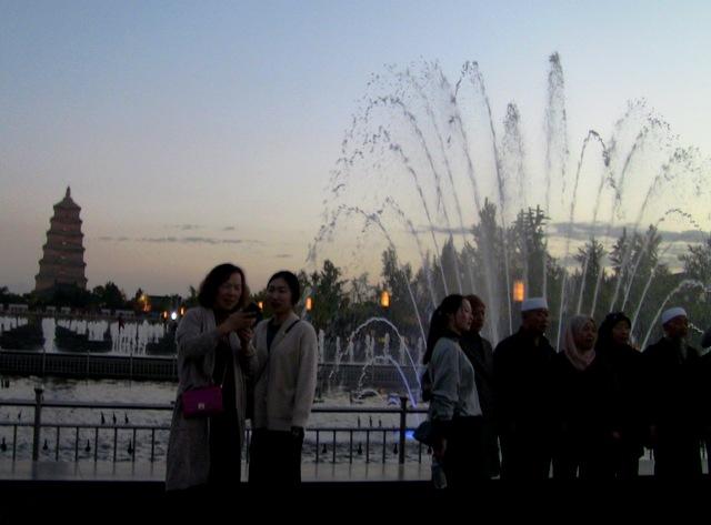 『 大雁塔広場の音と光と水の競演-噴水ショーが凄い! 』 ..大雁塔をバックに記念撮影です。あたりは夕闇に包まれています。..